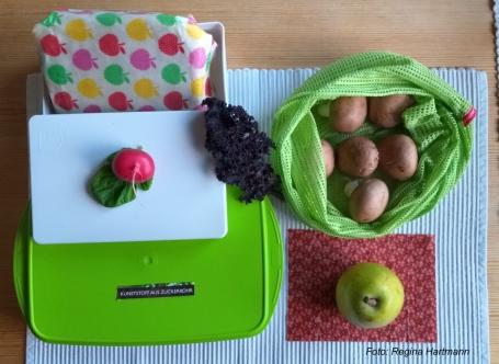 Eine Dose aus Zuckerrohr, Wachspapier für Käse und Wurst und Stoffsäckchen für Obst und Gemüse - Einkaufsalternativen helfen Verpackung einzusparen.