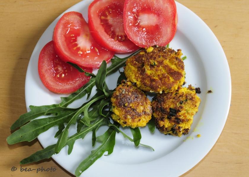 Tofufrikadellen mit Tomaten und Rucola serviert.