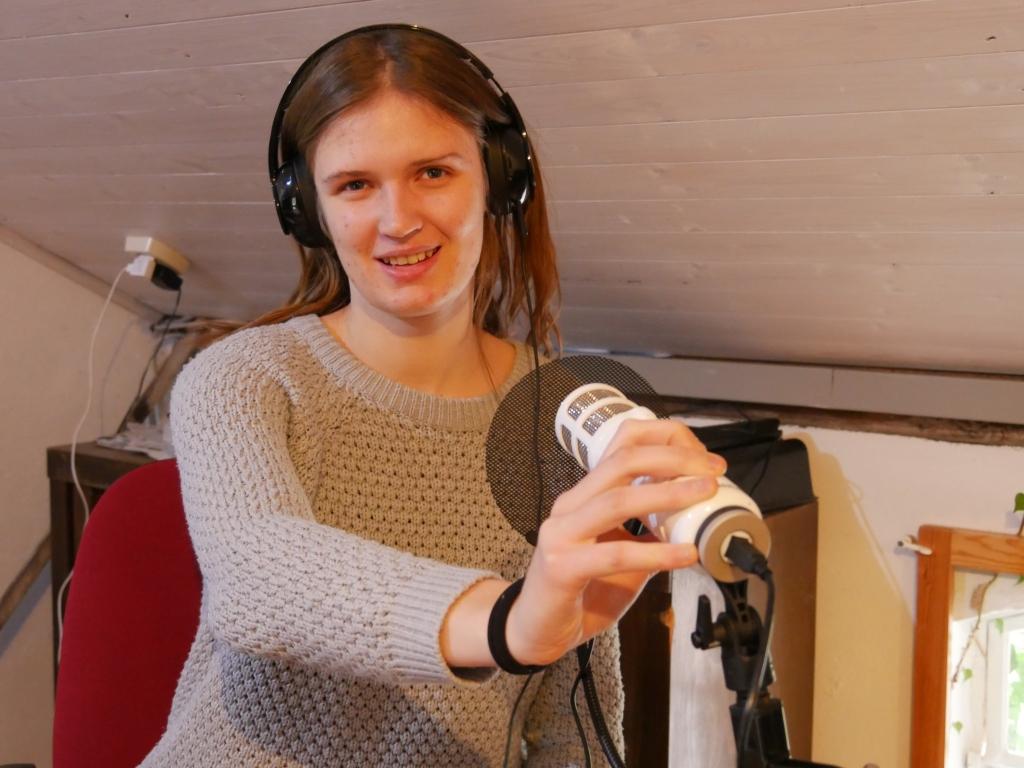 ie FSJlerin der Seefelder Mühle sitzt im Büro mit Kopfhrern und einem Mikrofon. So kann man sich eine Podcastaufnahme vorstellen